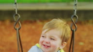 Adorable little boy on a swing in slow motion, with a big smile on his face video