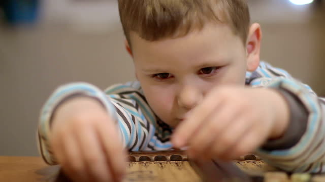 adorable little boy playing backgammon indor video