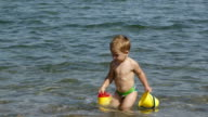 Adorable little boy playing in the sea video