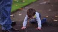 Adorable little boy trips and falls while walking, starts crying, and his dad picks him up video