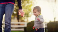 Adorable little boy walking in a park and holding his mother's hand video