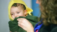 Adorable little boy wrapped in a towel as his mom dries off his face video
