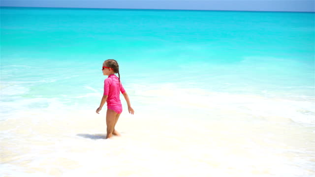 Adorable little girl at beach having a lot of fun in water video