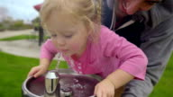 Adorable little girl drinks from a fountain video