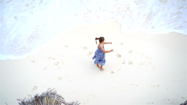 Adorable little girl having a lot of fun in shallow water.View from above of a deserted beach with turquoise water video