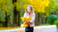 Adorable little girl outdoors at beautiful autumn day playing with leaves video