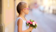 Adorable little girl with flowers bouquet walking in european city outdoors video