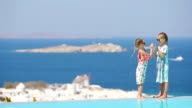 Adorable little girls playing in the edge of outdoor swimming pool with amazing view of old Mykonos town, Europe video