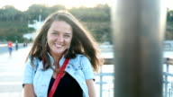 Adorable young woman looking at camera and having fun on a bridge near the sea video