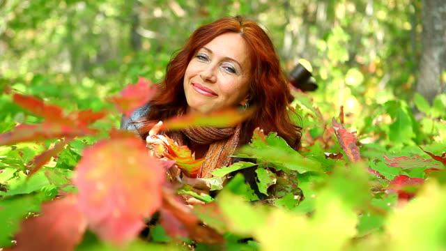 Adult beautiful woman among autumn oak seedlings video