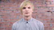 Adult blonde man try depict fright, fear, dread on camera. Brick wall. Audition video