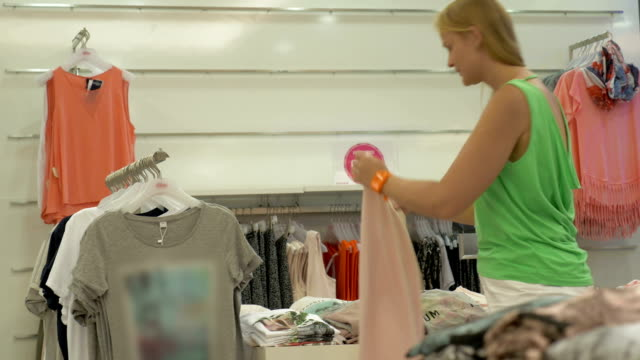 Adult blonde woman looking for t-shirt in clothes shop video