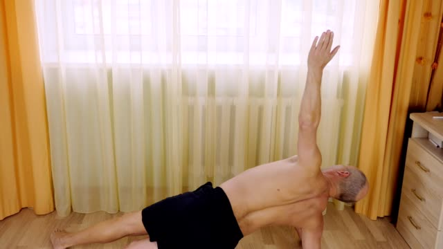 Adult caucasian man do plank exercise at home living room on floor. Training core muscles. video
