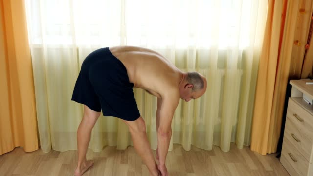 Adult caucasian man do stretching yoga pilates exercise at home living room. Tilt forward to legs. video