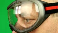 Adult caucasian man in protective eyeglasses profile. Extreem close-up view of male face in glasses. Worker in goggles in profile. A scientist with glasses. Skier or biker. Eyes and glasses close up video
