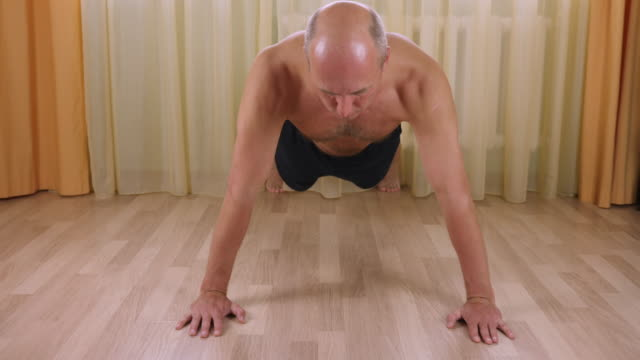 Adult caucasian man pushing up from floor at home living room. Workout training. Front view close up video