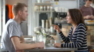 Adult couple talking at a table in a coffee shop, side view video