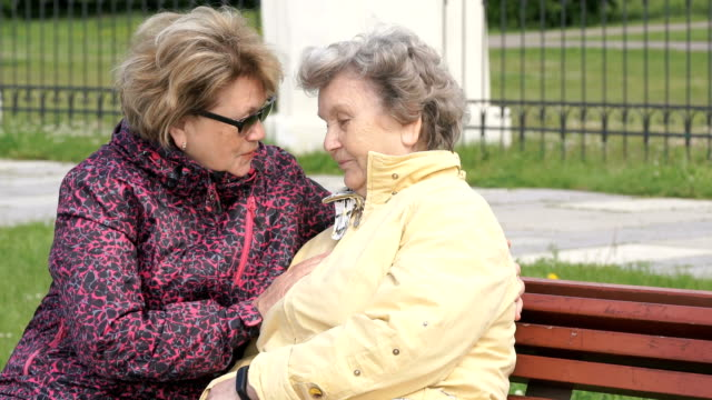 Adult daughter soothes old mother during stress video