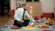 Adult male businessman collects children's building-block and enjoys sitting on the floor in the nursery. video