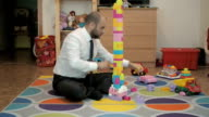 Adult male businessman collects children's building-block and enjoys sitting on the floor in the nursery. Time Lapse. video