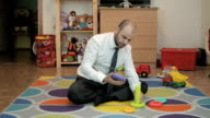 Adult male businessman collects children's pyramid and enjoys sitting on the floor in the nursery. video