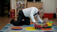 Adult male businessman playing toy cars sitting on the floor in the nursery. video