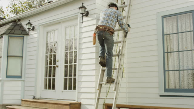 Adult male construction worker making repair on residence video