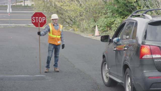 Adult male road flagger is cheerfully flagging a vehicle on a neighborhood road video