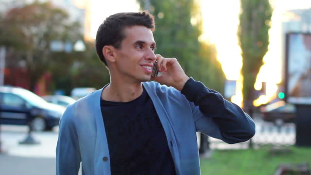 Adult male talking over phone enjoying conversation daytime park video