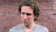 Adult man depict sincerely sympathy and sadness on camera. Brick wall. Audition video