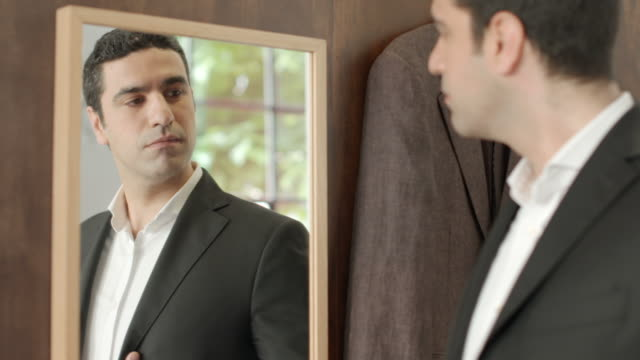 Adult man dressing up and looking at mirror, fashion store video