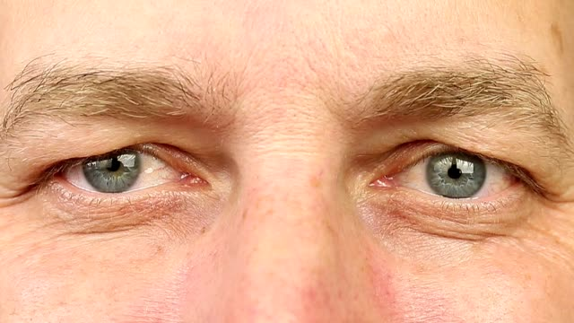 Adult man laughing with eyes. Extreme close-up view. Wrinkles around the eyes from laughing. The man's eyes narrowed. Human eyes fast open up and shut down. Caucasian male face close open eyes. video