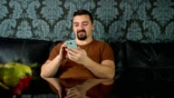 Adult man sitting on a sofa in the living room and using a smart phone video