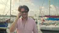 Adult Man Talking with Phone and Walking at the Marine video