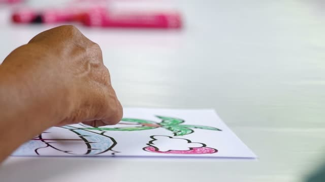 adult person painting on the paper with crayon video