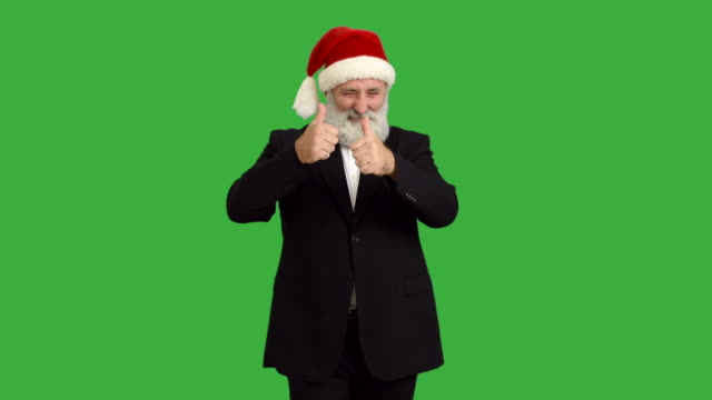 adult senior beard man dancing and calling to him  in a hat santa claus  on a green background video