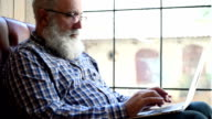 Adult senior bearded man sitting with a laptop video