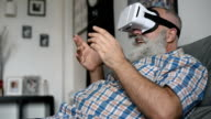 adult senior man and a virtual reality headset. graybearded man using vr glasses video
