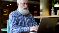 Adult senior man sitting with a laptop  smiles affably. video