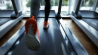 Adult sport woman running on treadmill in gym - color graded footage video