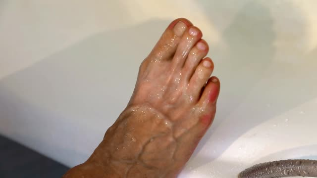 Adult white caucasian man checks athletes foot between toes in bath. Zoom foot fungus between toes. video