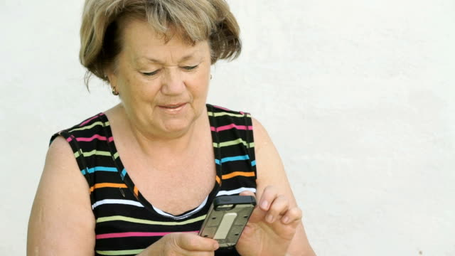 Adult woman holding a smart phone outdoors video