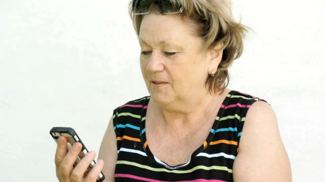 Adult woman talking with husband using smart phone video