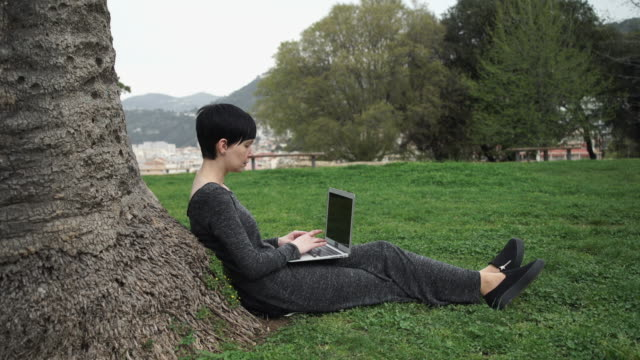 Adult woman working on the computer in the park under tree video