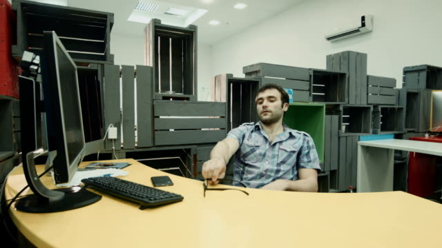 Adult worker relaxing after workday using cell and throwing paper ball video