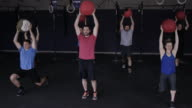 Adults doing a lunging workout together with a medicine ball video