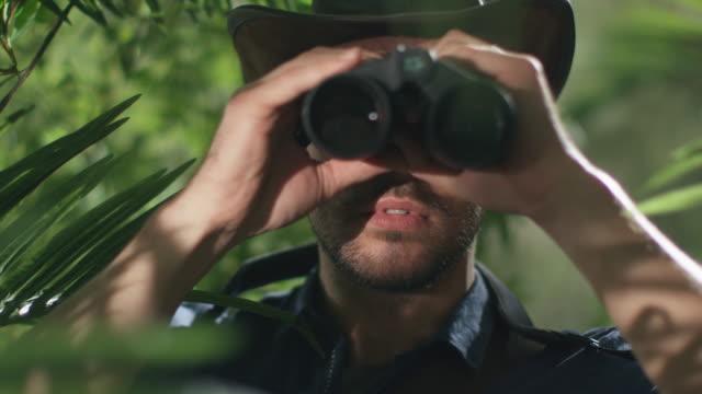 Adventurer in Hat Walking through Jungle Forest And Looking through Binoculars video