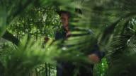 Adventurer in Hat Walking through Jungle Forest video