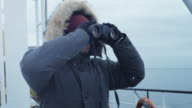 Adventurer in Warm Jacket Standing on Ship and Looking through Binoculars. It is Snowy and Windy video