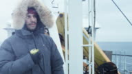 Adventurer in Warm Jacket Standing on Ship and Using Radio for Communication. It is Snowy and Windy video